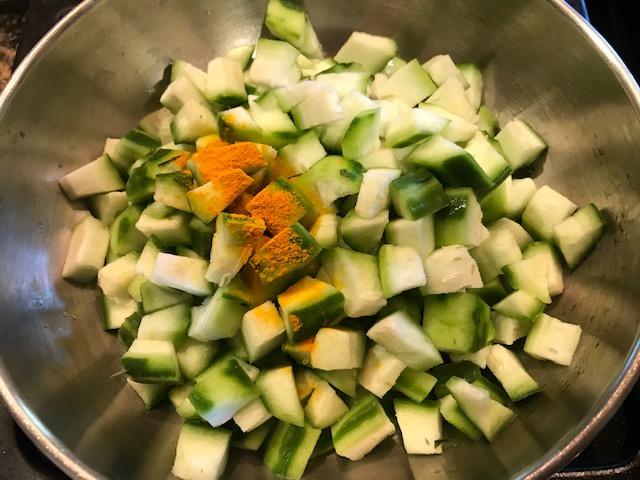 cooking ridge gourd curry or turai ki subji with turmeric