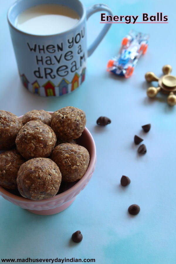 energyballs served in a pink bowl, on teh side are milk, few chocoalte chips and kids toy car