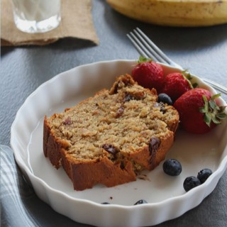 moist banana bread topped with chocolate chips and served with some berries