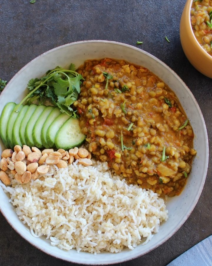 green moong dal curry served with rice, peanuts and cucumber.