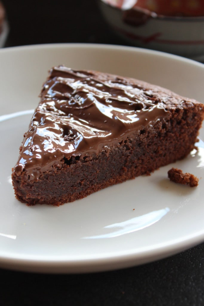 slice of nutella cake with nutella frosting on a white plate