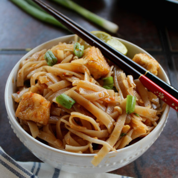 vegan pad thai noodles served in a white bowl with chap sticks
