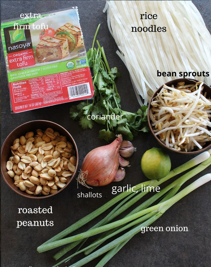 rice noodles, tofu, peanuts, shallots, like, garlic and bean sprouts on a black surface