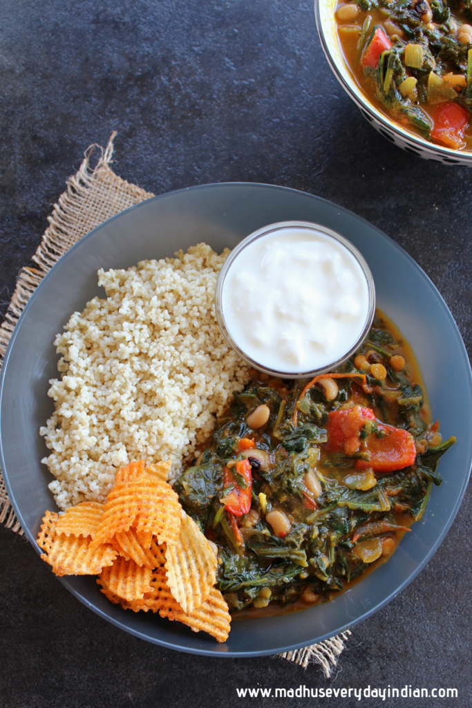 spinach stew served in a black bowl with millets, chips and yogurt