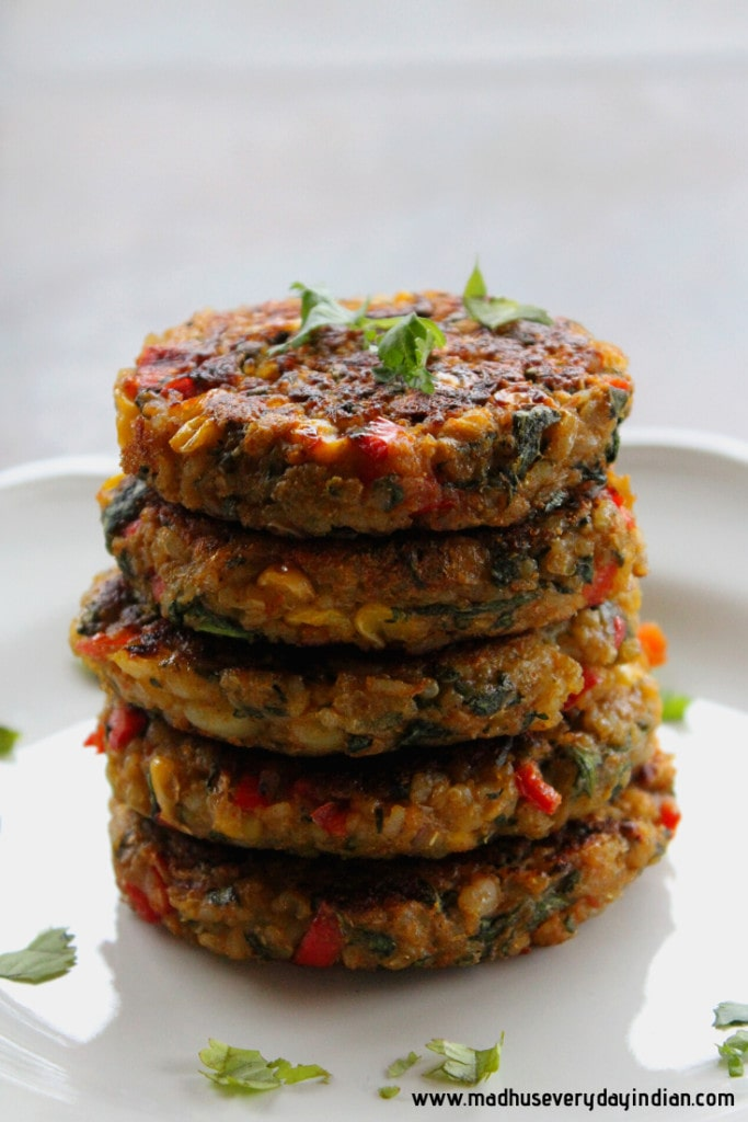 stacked veggie quinoa brown rice patties on a white plate and garnished with cilantro