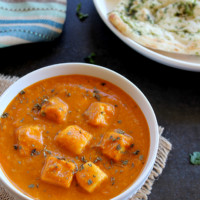 paneer butter masala served in a white bowl with naan and rice