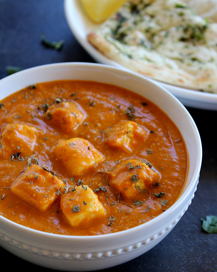 paneer makhani served in a white bowl with naan