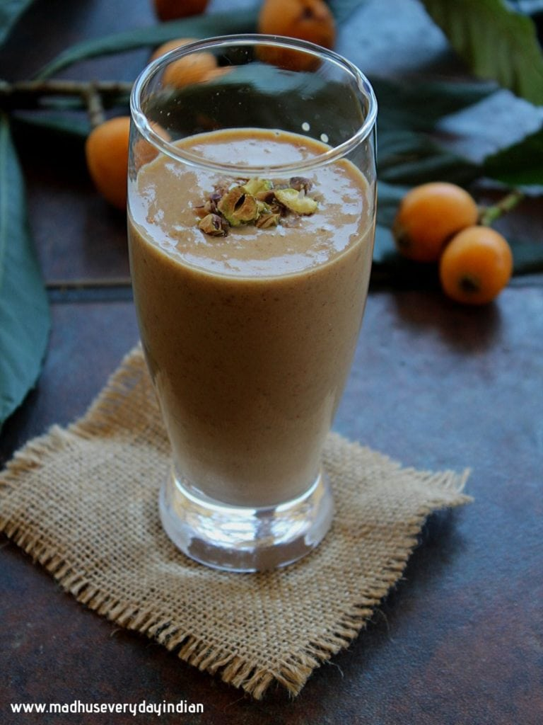 loquat smoothie served in aglass jar and topped with nuts