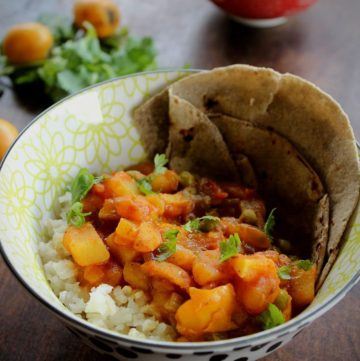 potato loquat curry serve with rice and roti in a bowl