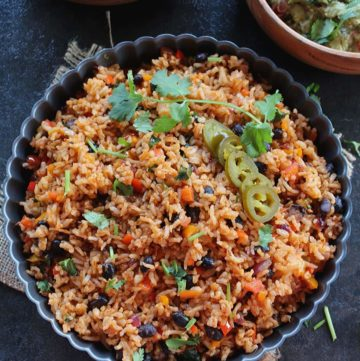 mexican rice served in a grey large bowl and garnished with jalapeno and coriander leaves