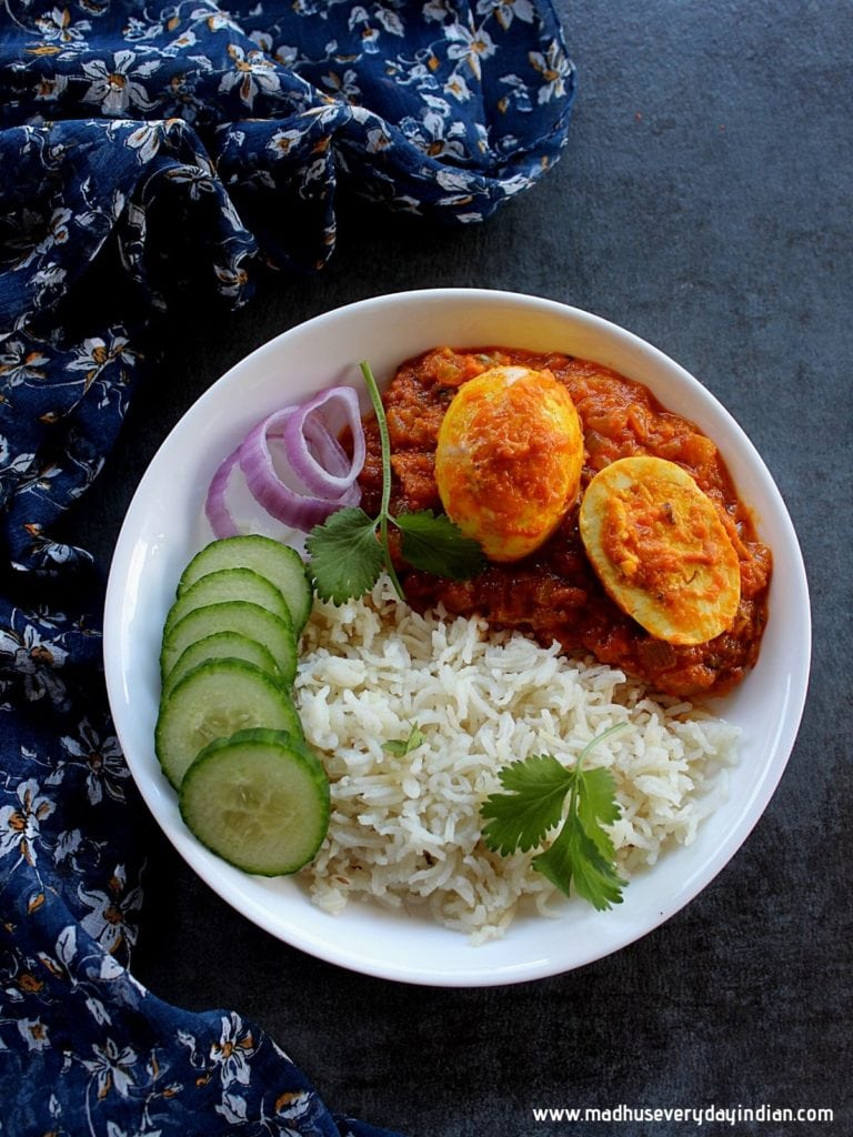 egg curry served with rice,cucumber, onion in a white plate and garnished with cilantro