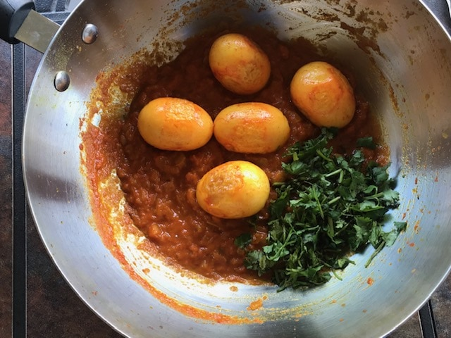 pan fried eggs and coriander leaves added masala mixture