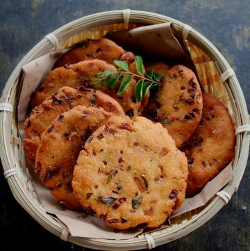 maddur vada served in a small basket and curry leaves on the side
