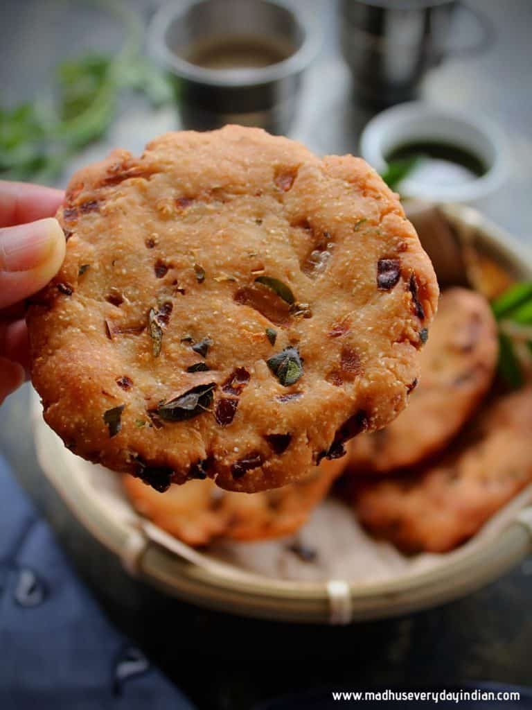 crispy maddur vada held in the hand and in the back ground are more vada, coffee and chutney