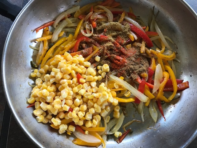 corn and spices added to the onion bell pepper mixture