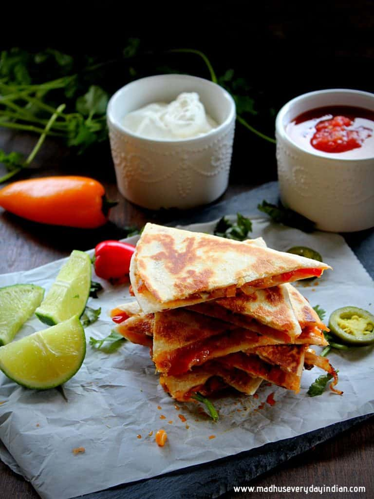 stacked veggie quesadilla served with lime wedges, sour cream and salsa
