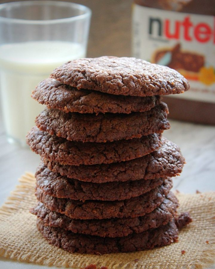 stacked nutella cookies served with cup of milk and nutella bottle in the back ground