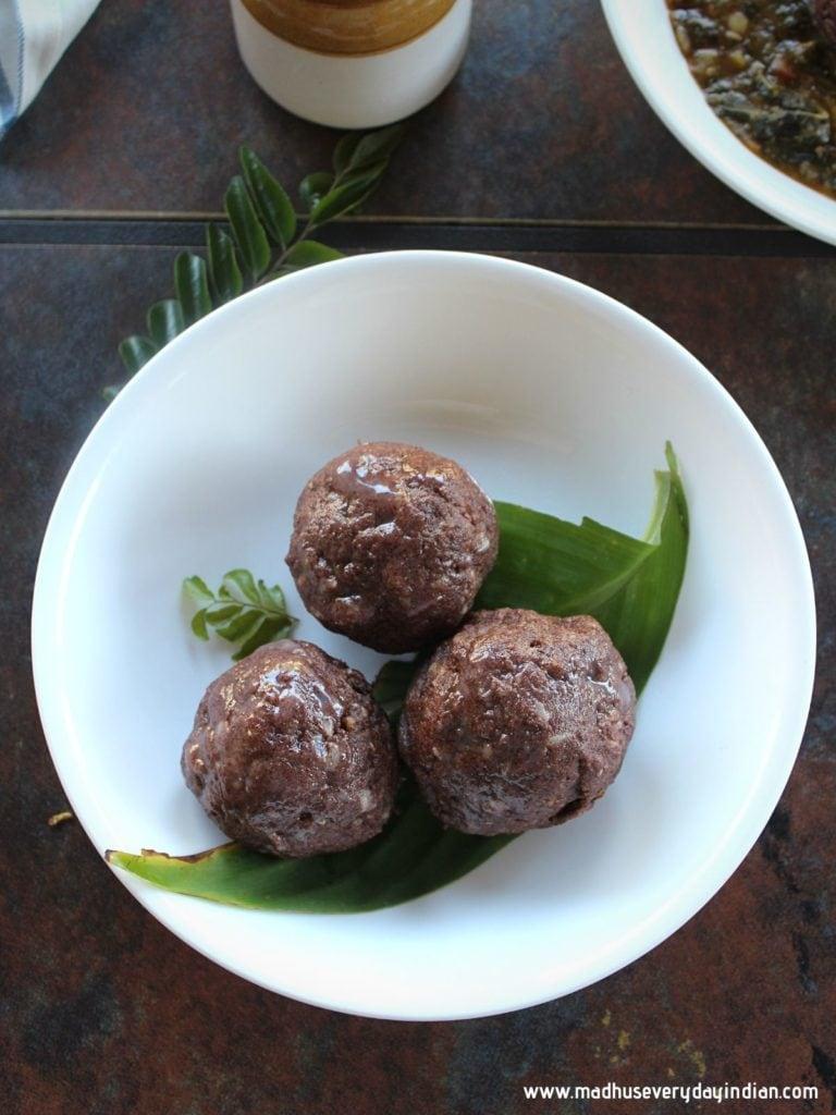 3 ragi mudde balls served in a white plate on al leaf