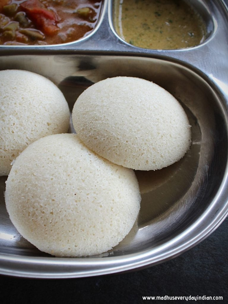 3 idlis served in a steel plate with chutney and sambar