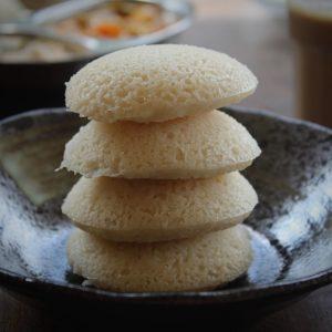 4 idli stacked in black bowl