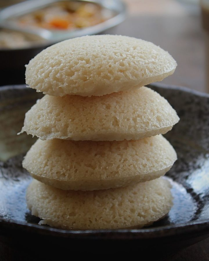4 idli stacked in black bowl