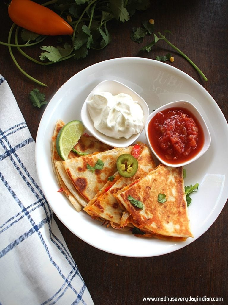 vegetable quesadillas served with sour cream, salsa and lime wedge
