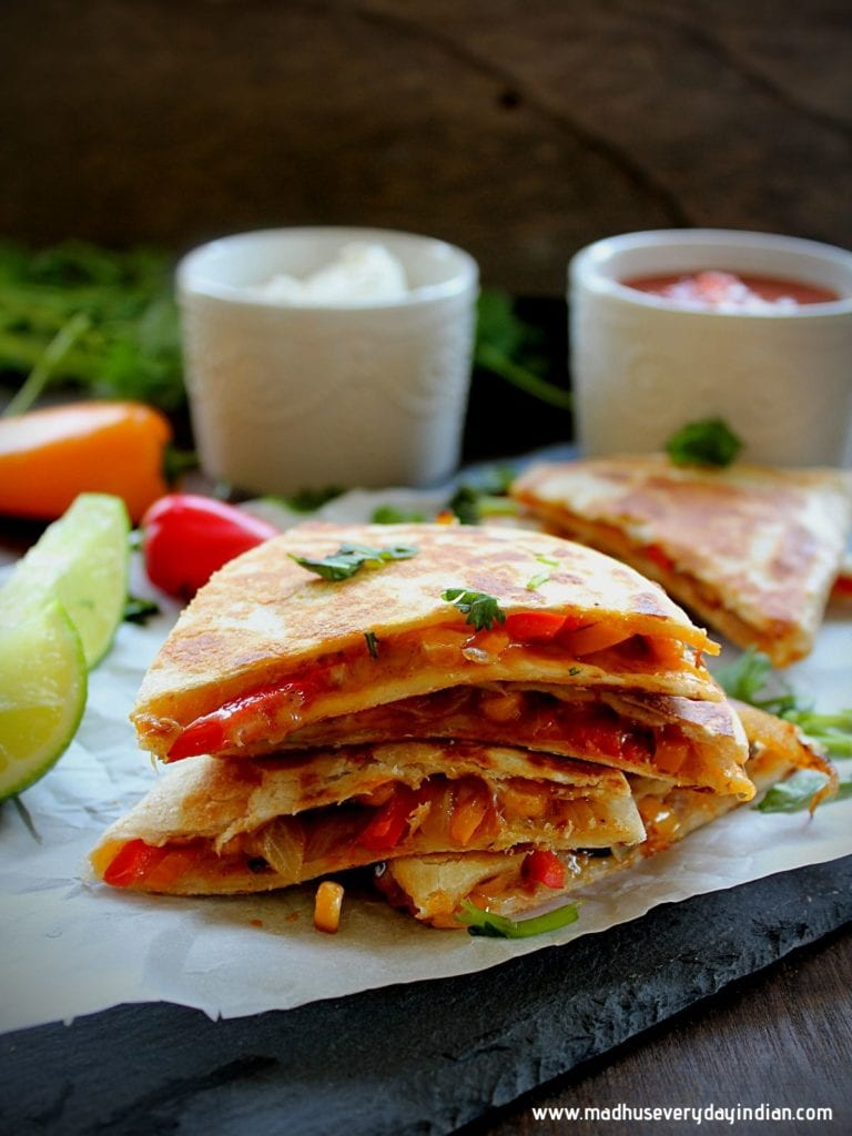 stacked vegetable quesadilla  oozing out cheese and served with few sides
