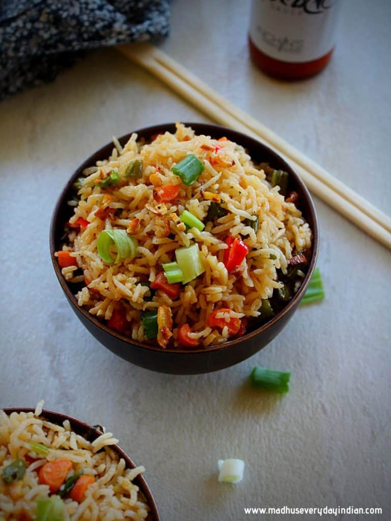 burnt garlic fried rice served ina wooden bowl with green onion, chop sticks and chili sauce