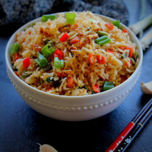 burnt garlic fried rice served in a white bowl and chop sticks and garlic pod on the side.
