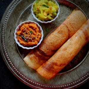 crispy dosa served with onion chutney and potato fry in a plate