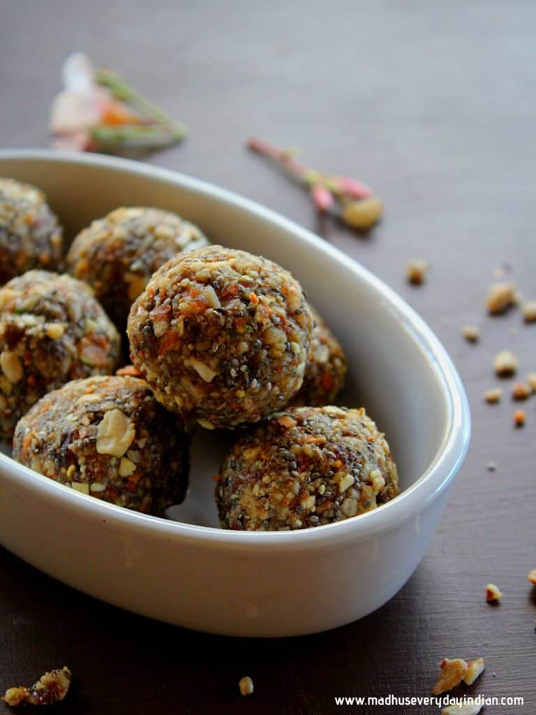 dry fruit laddu served in a white bowl and few crushed nuts are garnished