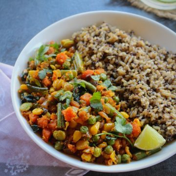 quinoa and brown rice served with mixed vegetable fry on a white plate with some lime