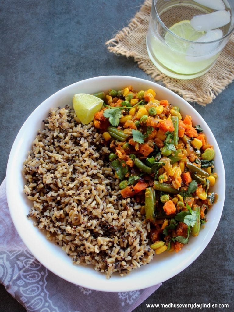 quinoa and brown rice served with mixed vegetable fry on a white plate with some cold water and slice of lemon