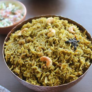 palak biryani served in a bowl and in the background is raita