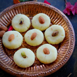 malai peda swerved in a plate with almonds and few flowers for garnish