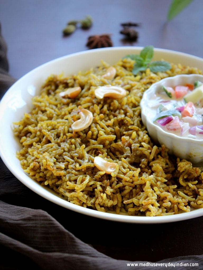 palak biryani served in a bowl with raita