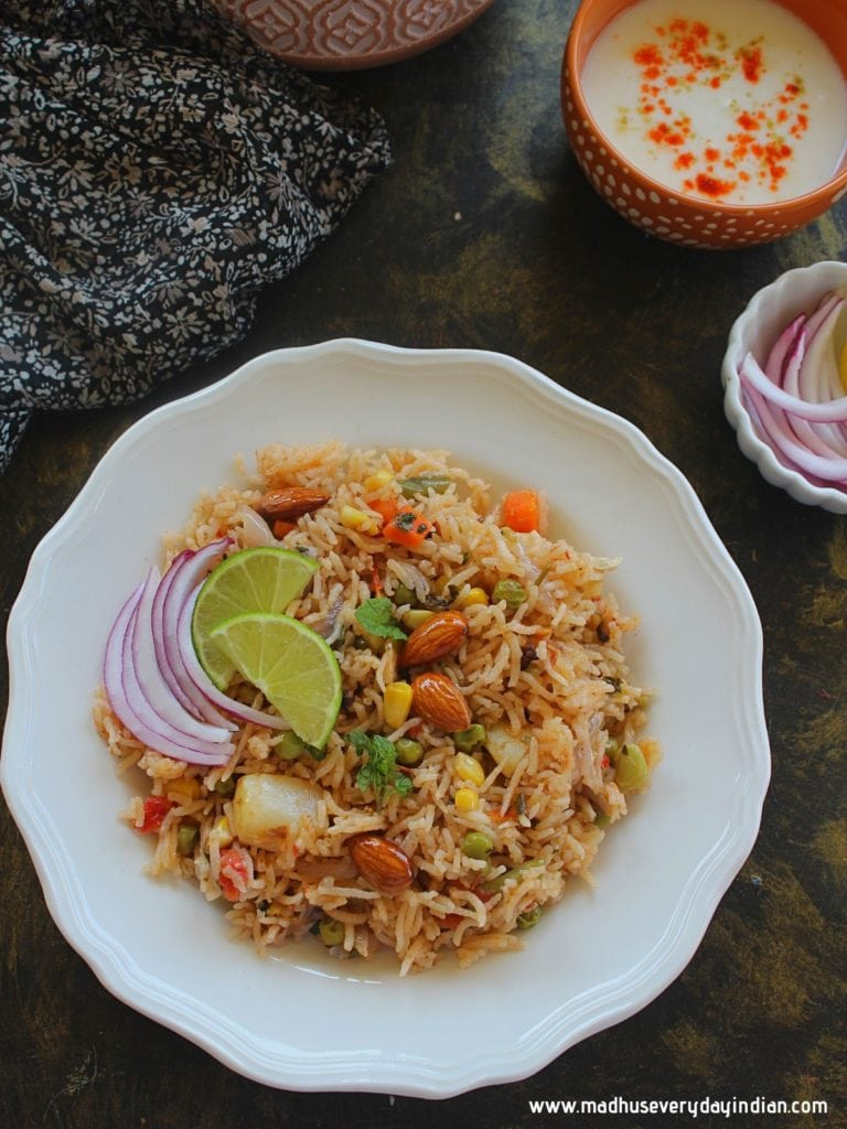 vegetale pulao served in a white plate with onion, lime and yogurt