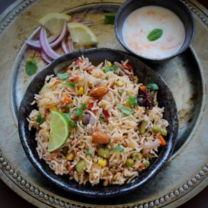 vegetale pulao served in a black bowl and served with onion, lime and yogurt