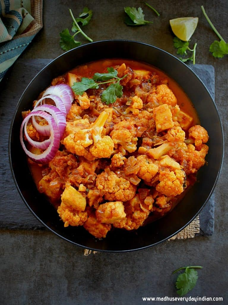 cauliflower paneer curry served in a black blwol garnished with onion and corinader leaves and lemon on the side