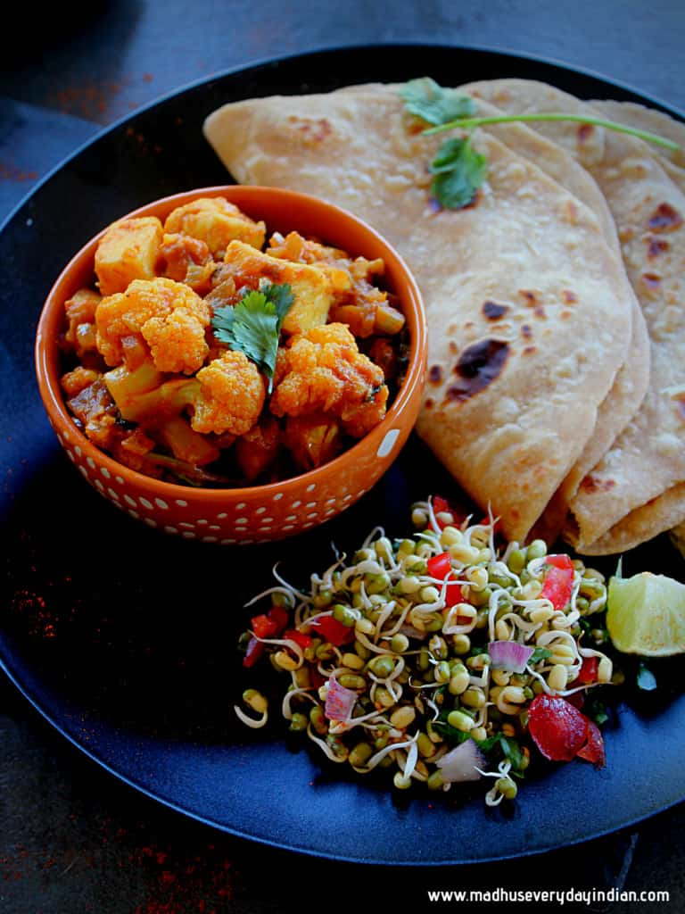 cauliflower paneer curry served with chapathi and sprouts salad on a large black plate garnished with coriander and lemon