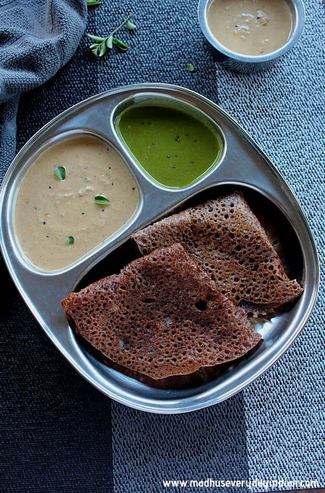 2 ragi dosa's served in a steel palte with coconut and peanut chutney