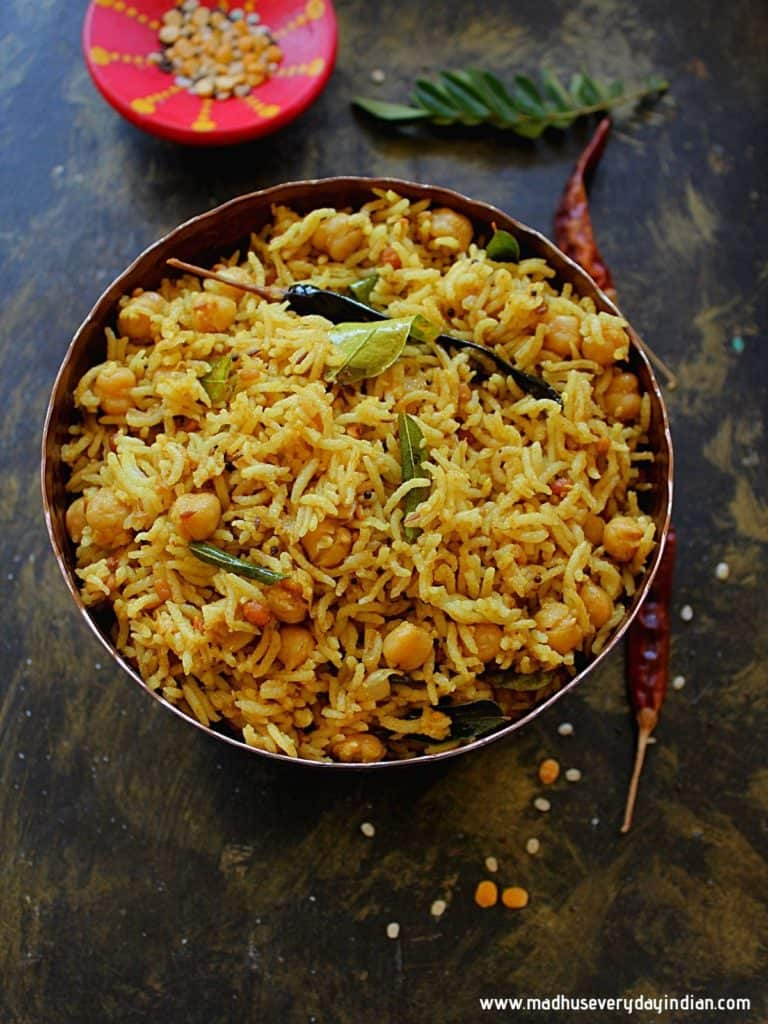tamarind rice served ina  copper bowl garnished with curry leaves