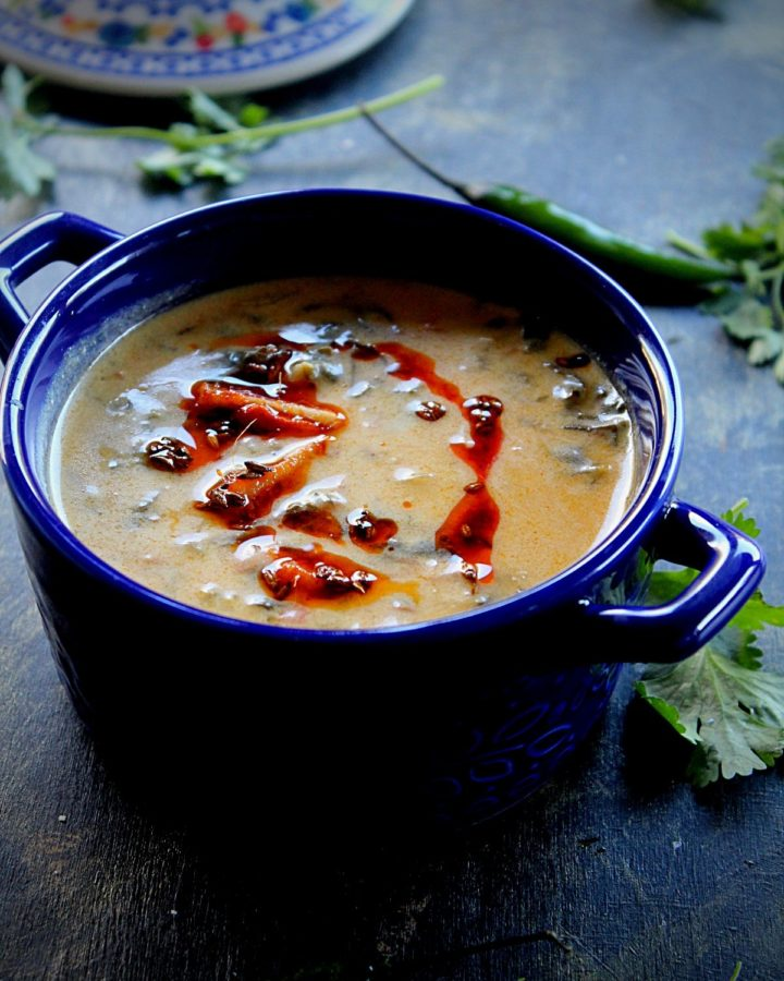 palak kadhi served in a blue bowl garnished with red chili powder and cilantro