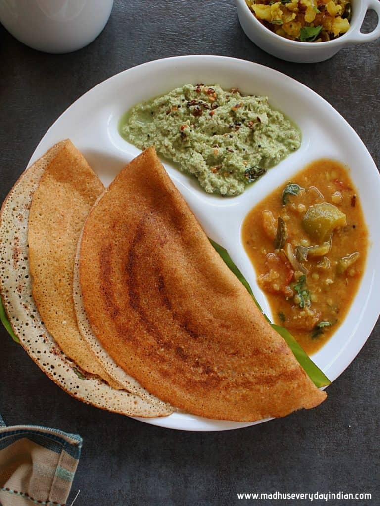 wheat dosa served in a steel plate with coconut chutney, potato fr and sambar