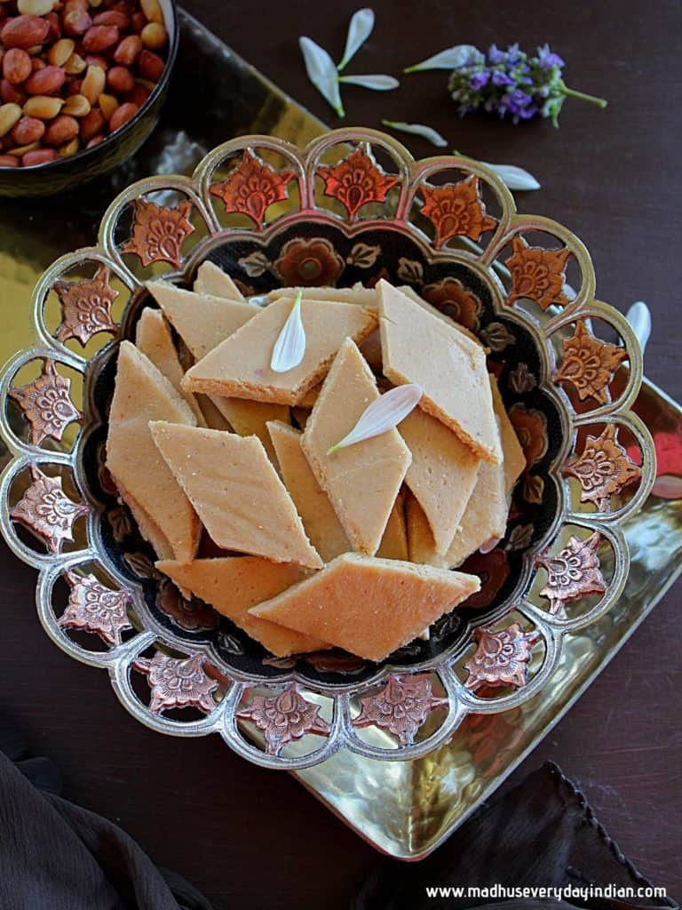 peanut katli stacked in afancy bowl with roasted peanuts in the background
