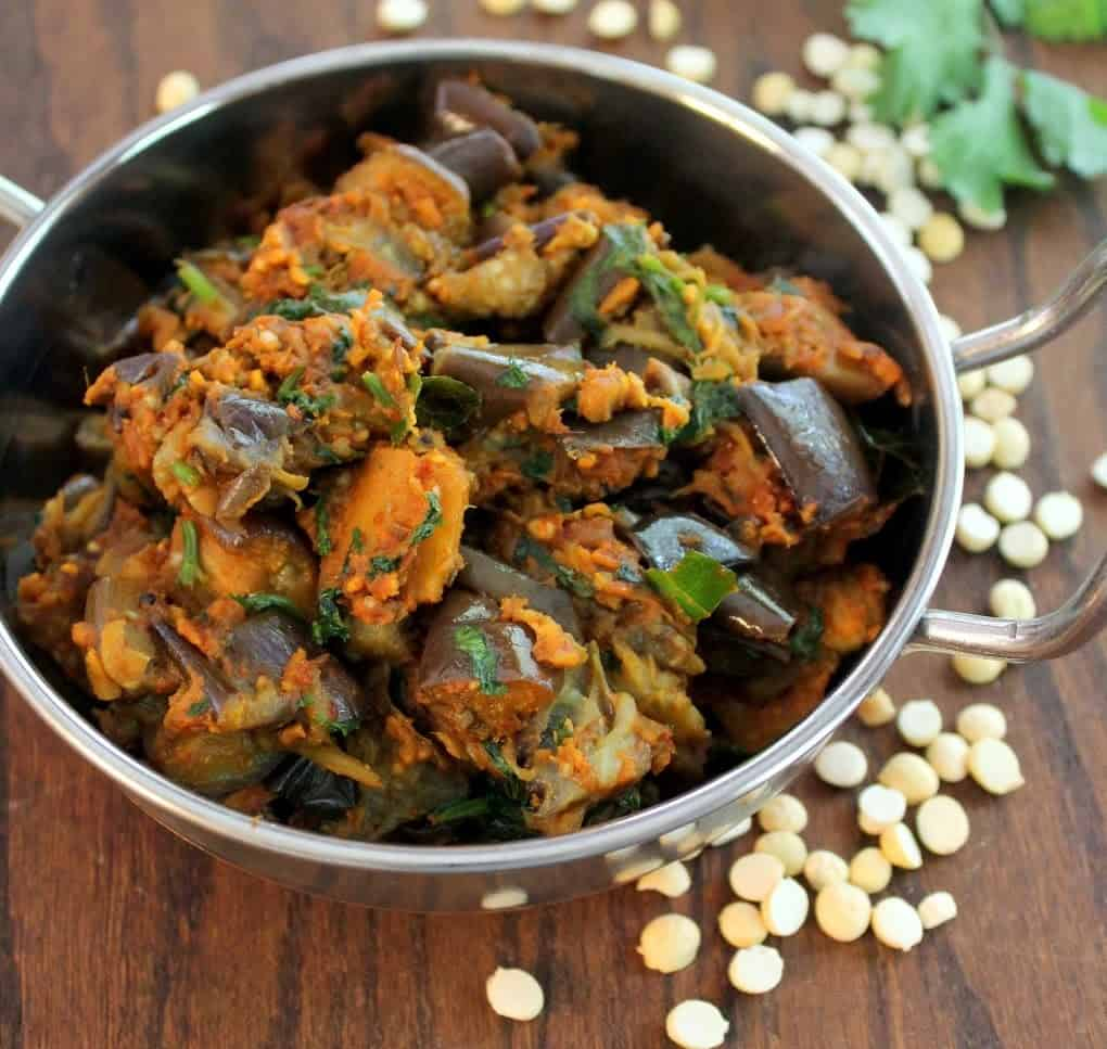 brinjal masala served in a steel pot and garnished with coriander leaves