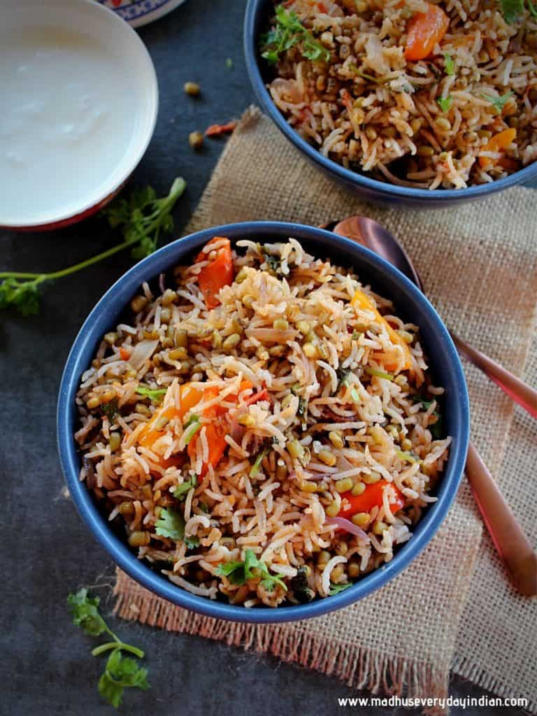green moong dal pulao served in blue bowls with a bowl of plain yogurt on the side