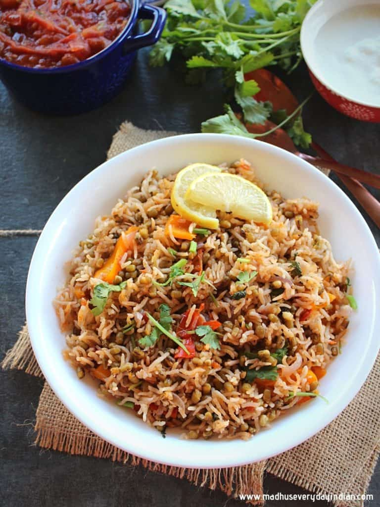 green gram pulao served in a white plate with lemon wedges