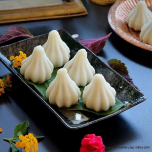 steamed modak served in a black plate and flowers on the side