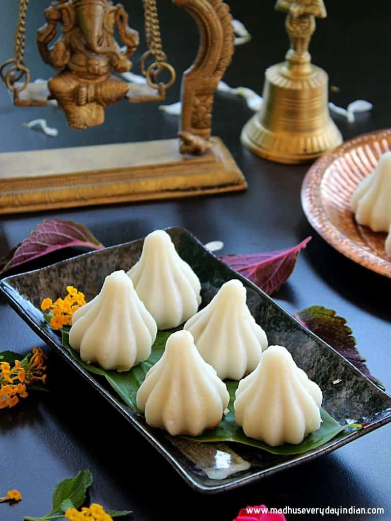 steamed modak placed in a black plate and in the back ground is an idol of lord Ganesha